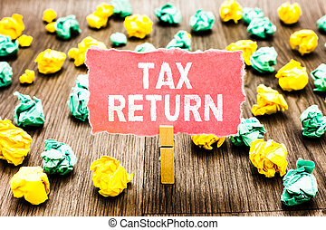 Word writing text Tax Return. Business concept for which taxpayer makes annual statement of income circumstances Clothespin holding pink note paper crumpled papers several tries mistakes.