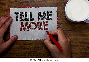 Word writing text Tell Me More. Business concept for A call to start a conversation Sharing more knowledge Man holding marker communicating ideas piece paper wooden table cup coffee.