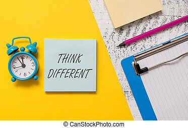 Word writing text Think Different. Business concept for be unique with your thoughts or attitude Wind of change Notepads clipboard colored paper sheet marker alarm clock wooden background.