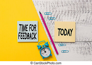 Word writing text Time For Feedback. Business concept for information about reactions to a product or services Notepads marker pen colored paper sheet alarm clock wooden background.