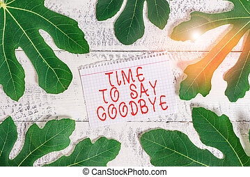 Word writing text Time To Say Goodbye. Business concept for Bidding Farewell So Long See You Till we meet again Leaves surrounding notepaper above a classic wooden table as the background.