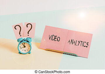 Word writing text Video Analytics. Business concept for analyzing video to detect and determine temporal event Mini size alarm clock beside a Paper sheet placed tilted on pastel backdrop.
