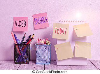 Word writing text Video Conference. Business concept for showing in remote places hold facetoface meetings 6 Sticky Notes on Wall Open Spiral Notebook 2 Pencil Pots on Work Desk.