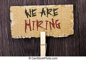 Word writing text We Are Hiring. Business concept for Talent Hunting Job Position Wanted Workforce HR Recruitment written on Cardboard Piece Holding With Clip on the wooden background.