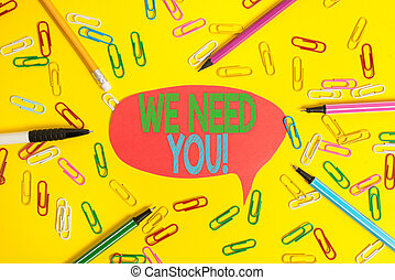 Word writing text We Need You. Business concept for asking someone to work together for certain job or target Flat lay above empty paper with copy space pencils and colored paper clips.