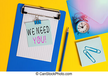 Word writing text We Need You. Business concept for asking someone to work together for certain job or target Clipboard sheet note binder pencil clips clock envelop colored background.