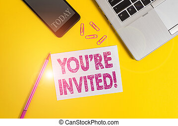 Word writing text You Re Invited. Business concept for make a polite friendly request to someone go somewhere Trendy open laptop smartphone marker paper sheet clips colored background.