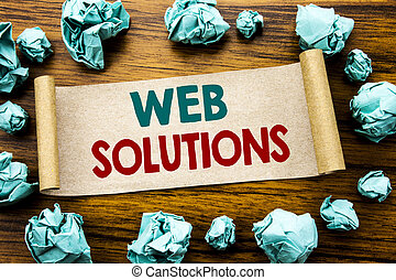 Word, writing Web Solutions. Business concept for Internet Design Plan Written on sticky note paper, wooden background with folded yellow paper meaning thinking