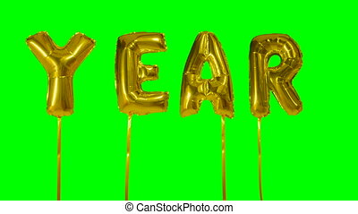 Word year from helium golden balloon letters floating on...
