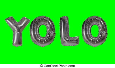 Word YOLO from helium silver balloon letters floating on...