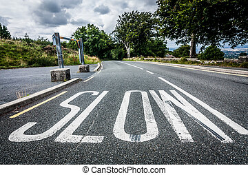 Worded marking SLOW painted on the road to warn drivers to...