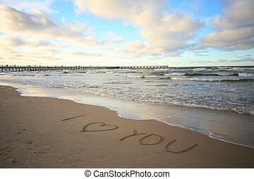 Words about love written on wet sand