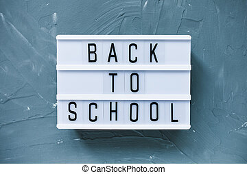 Words BACK TO SCHOOL on a gray background. Education concept, flat lay, top view, social media hero header template, copy space.