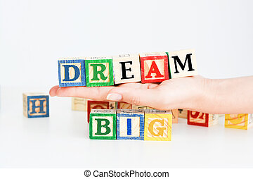 "Words ""dream big"" spelled with wooden letter cubes"