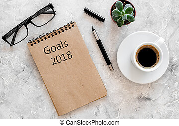 Words Goals for 2018 writting in notebook near glasses and...