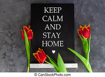 Words Keep Calm And Stay Home on chalkboard on grey concrete background with fresh tulips. Motivation banner text