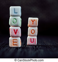 Words Love You written in ceramic blocks on brown wooden background