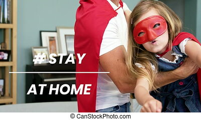 Words # Stay At Home written over a man playing with his daughter during quarantine with coronavirus