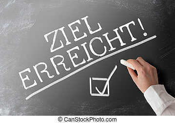 words ZIEL ERREICHT, German for goal accomplished, with checkmark on chalkboard