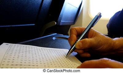 Wordsearch in flight - Woman hand holding a pen is crossing ...