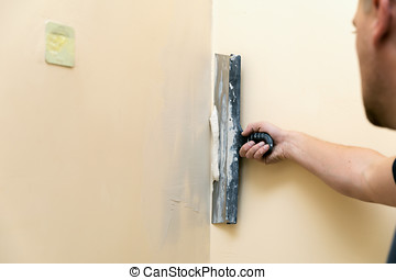 work aligns - worker plastering wall with spatula