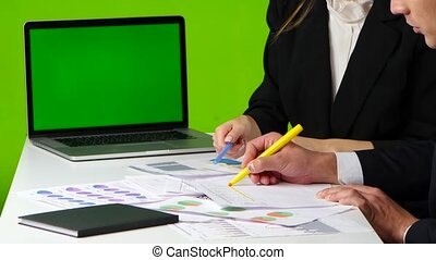 Work desk in the office, man and woman draw a graph, open notebook with green screen