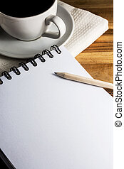 work desk with paper, pencil and white cup of coffee