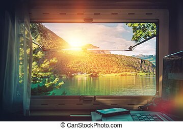 Work Desk with Scenic View. Working in the Camper Van Motorhome While Traveling During Vacation Time. Working on Laptop Inside RV Motorcoach.