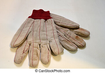 Work gloves - A pair of soiled work gloveswith red trim lays...