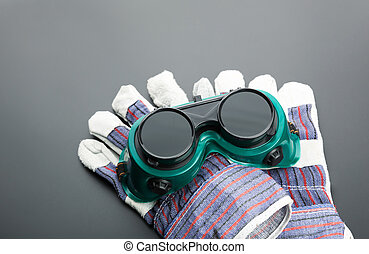 Work gloves and protective glasses on grey background