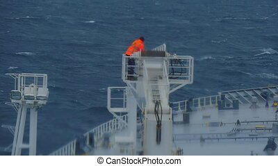 work in hazardous conditions on a ship in a cargo crane. A man in a jean jacket and a cargo crane on an oil tanker