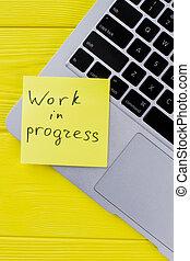 Work in progress concept. Laptop keyboard on yellow wood. ...