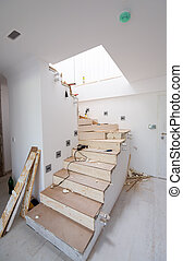 work in progress on stylish interior with wooden stairs in ...