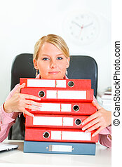 Work is done! Smiling modern business woman sitting at office desk with pile of folders