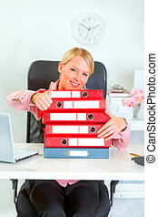 Work is done! Smiling modern business woman with pile of folders showing thumbs up