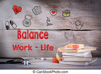 Work Life Balance Concept. Stack of books and a stethoscope on a wooden background