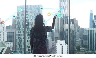 Work of an IT specialist woman before which a hologram of the problem is being developed stands by panoramic window against the backdrop of modern office buildings.