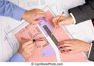 Above view of engineers hands over blueprints during discussion