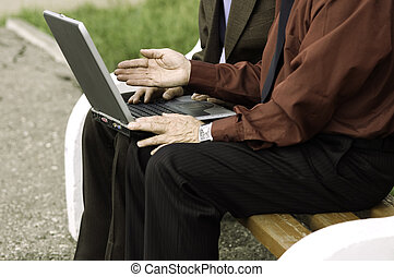 work on laptop - two businessmen with computer outside