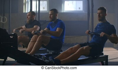 Work on the muscles of the back. Three Men working out on rowing machine in gym. 3 Men on the exercise machine with a weighting compound. The 3 man lifts heavy weight in the gym. Slow motion