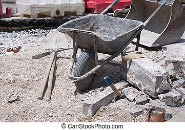 work on the road with wheelbarrow , a pick and hammer