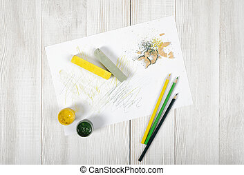 Work place of designer with colored pencils, brush, gouache jars, chalks and a white paper in top view