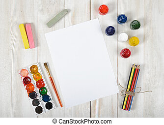 Work place of designer with colored pencils, brush, gouache jars, watercolor paints, chalks and a white paper in top view