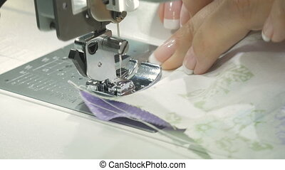 Work sewing machine, close-up. Female hands direct the...