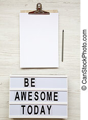 Work space with noticepad, pencil and 'Be awesome today' word on lightbox over white wooden background, top view. From above, flat-lay, overhead.
