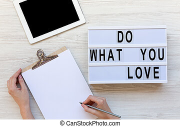 Work space with tablet, female hands, clipboard and 'Do what you love' word on modern board over white wooden background, top view. From above, flat-lay, overhead.