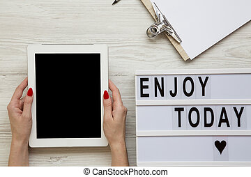 Work space with tablet, notepad and 'Enjoy today' word on lightbox over white wooden background, top view. Female hands hold tablet with blank screen. From above, flat-lay, overhead.