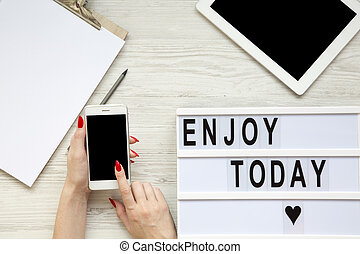 Work space with tablet, smartphone, notepad and 'Enjoy today' word on lightbox over white wooden background, top view. Female hands hold phone with blank screen. From above, flat-lay, overhead.