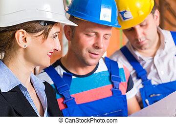Work Team on construction site controlling floor plan