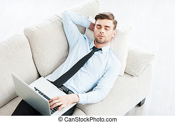 Work that makes him sleepy. Top view of young businessman sleeping and holding hand behind head while laying on sofa
